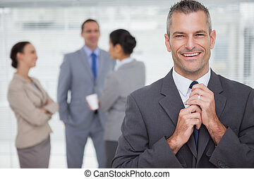 Smiling manager tidying his tie up with employees in background