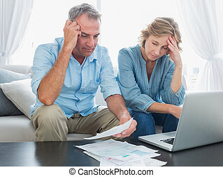 Worried couple paying their bills online with laptop