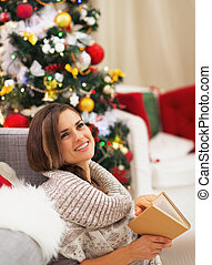 Thoughtful young woman with book near christmas tree