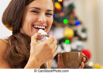 Happy young woman in pajamas having snack near christmas...
