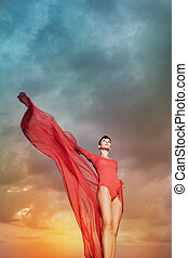 Beautiful woman with red chiffon in front of cloud...