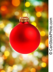 red christmas ball hanging on colorful bokeh background