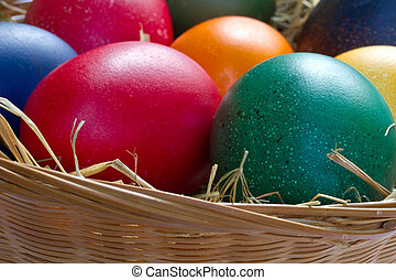 Colored easter eggs in a small basket, format filling