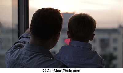 Happy father with his little son near the window