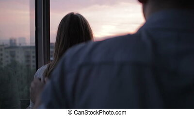 Young couple on the balcony at sunset