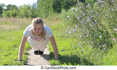 Young woman doing push ups in the park - Young woman...