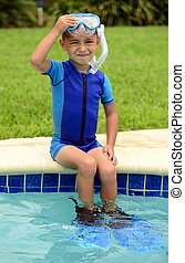 cute child sitting on edge of swimming pool