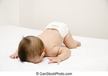 Face down lying baby on white bedroom