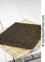 Dried seaweed on a makisu mat and table - A sheet of dried...