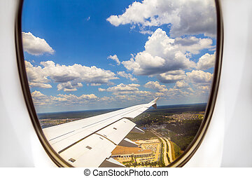 lookout of aircraft window to landscape while landing
