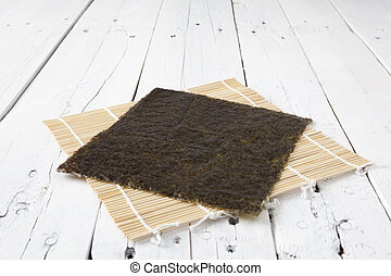 Nori on makisu and table - A sheet of dried seaweed Nori on...