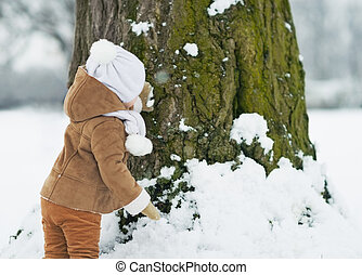 Baby playing with tree in winter . rear view