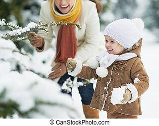 feliz, madre, bebé, juego, nieve, rama