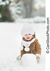 Happy baby making snowball for snowman