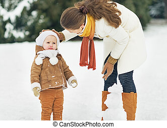 Mother and baby playing in winter outdoors