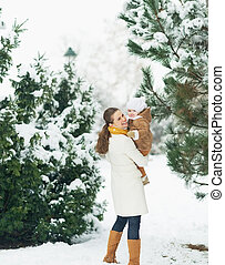 Happy mother and baby walking in winter park