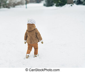 Baby walking in winter park . rear view