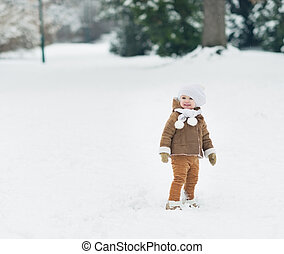 Smiling baby walking in winter park