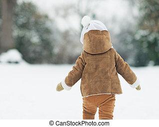 Baby walking in winter park . rear view