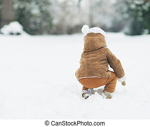 Baby playing with snow in winter park . rear view