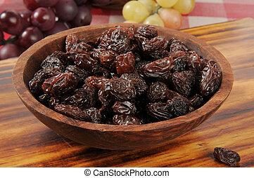 Bowl of raisins - Fresh raisins in a wooden bowl with a...