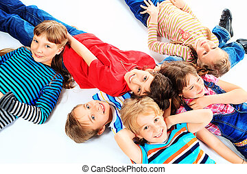 friends - Group of cheerful children lying on a floor...