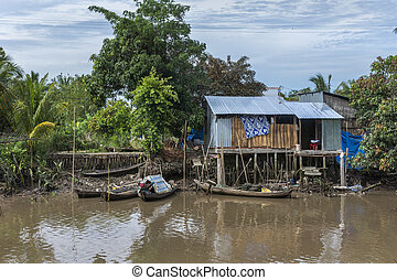 Small boats dock at a shack on stilts in the jungle.
