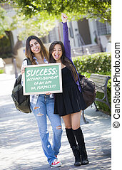 Excited Mixed Race Female Students Holding Chalkboard With Success and the Definition Written on it.