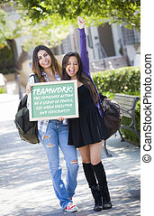 Excited Mixed Race Female Students Holding Chalkboard With Teamwork and the Definition Written on it.