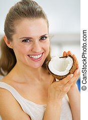 Portrait of happy young woman showing coconut