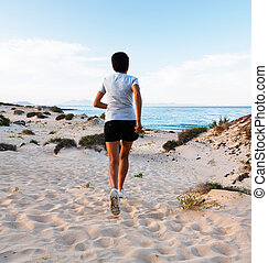 Woman running on beach - Athletic Asian woman runner jogging...