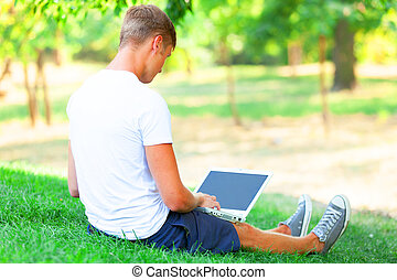 Teen boy with laptop in the park.