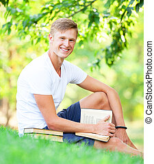 Teen boy with books and notebook in the park.