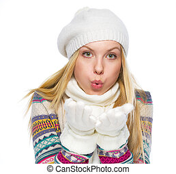 Teenager girl in winter clothes blowing snow from hands