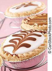 decorated tarts on a cake stand - with chocolate decorated...