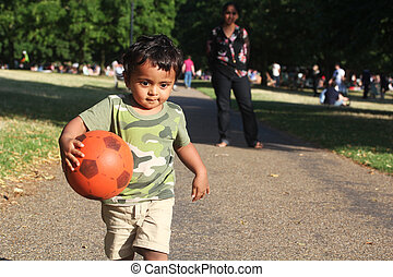 A Young asian or Indian Toddler running with a red ball in hand on a road alongside a green grass of a garden or a park