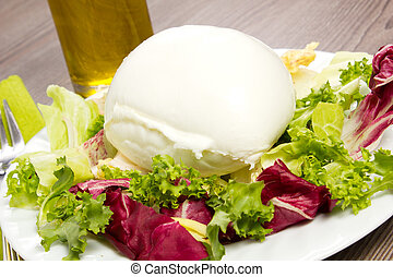 Italian mozzarella and salad on a wood table with oil
