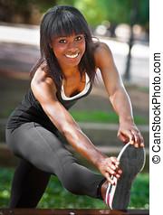 black girl prepares for sports in a public park