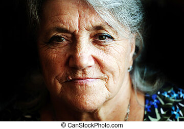 A portrait of a sad granny on a black background