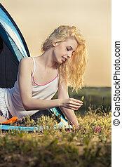 Beautiful blond woman camping