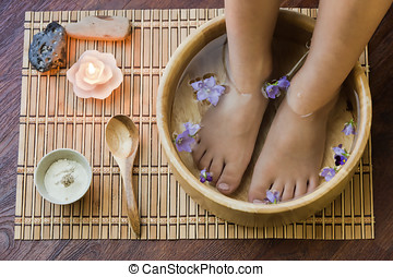 Soaking feet in wooden bowl.