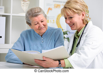 doctor and patient - doctor talking to her female patient at...