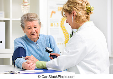 Medical exam - Doctor measuring blood pressure of senior...
