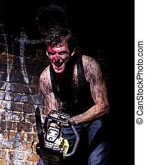 Horrific madman on a dark background and chainesaw -...