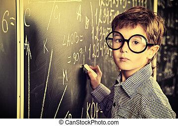 meet the blackboard - Portrait of a cute schoolboy in round...