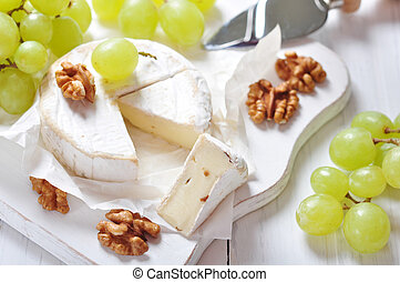 Camembert on wooden cutting board with grape and walnut...