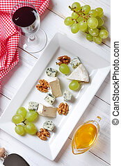 Camembert and blue cheese on plate with grape and walnut....