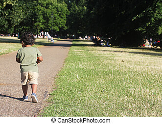 A Young Indian Toddler walking along a road along side green grass of a garden or a park