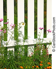 White fence whith green grass and flowers.