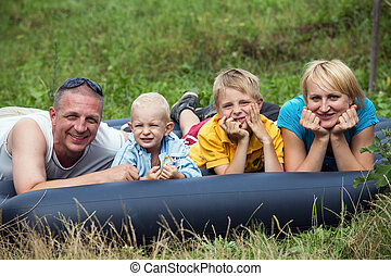 Happy mother, father and two sons in the park